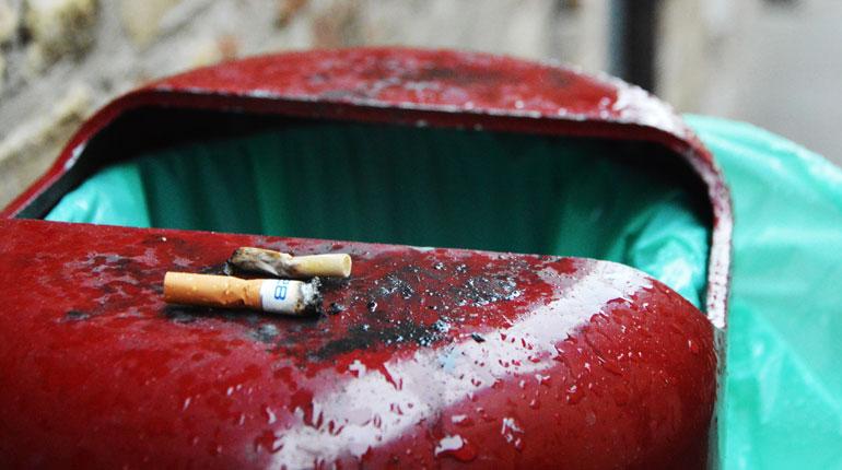 Sigarette spente e buttate su su un cassonetto per l'immondizia