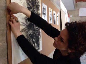 Laura Paja mentre attacca uno dei suoi disegni