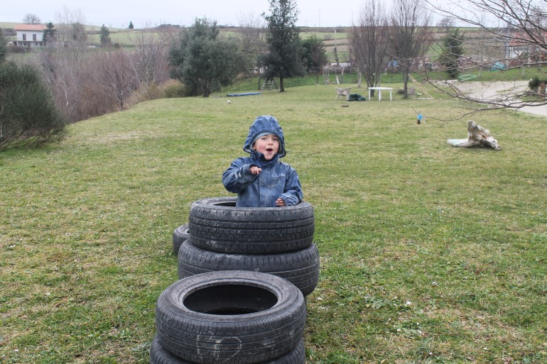 """Uno dei bambini di """"Maestra Natura"""" mentre gioca nel percorso costruito con pneumatici usati"""