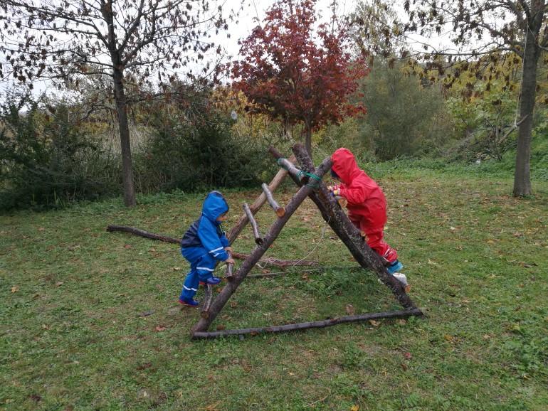 I bambini giocano con le strutture che hanno costruito con rami e corde