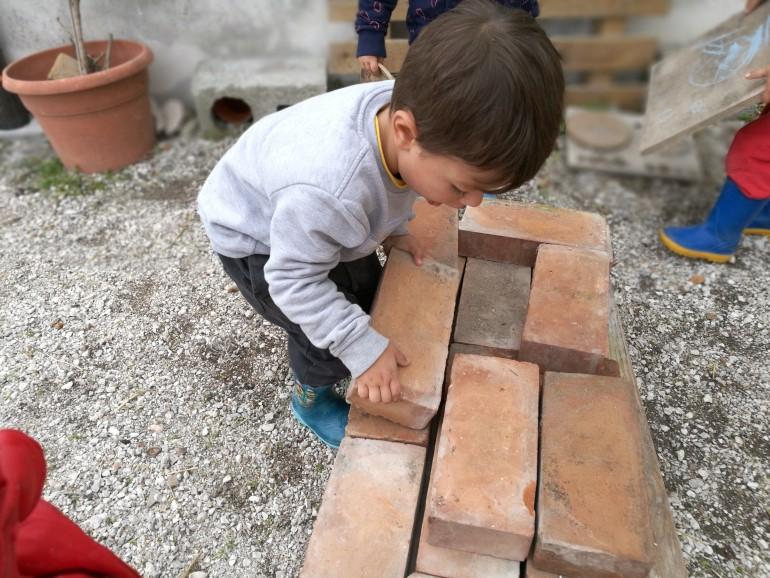 Uno dei bambini mentre costruisce un muretto